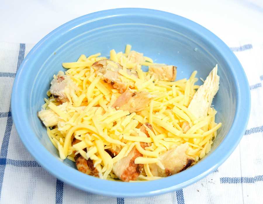 Cheese and chicken meat mixed up in a bowl for chicken quesadillas in the air fryer