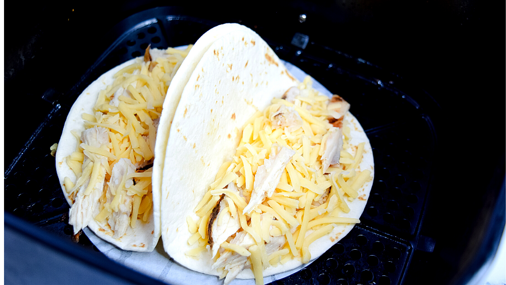 Two tortillas each filled with chicken and cheese in the air fryer basket.