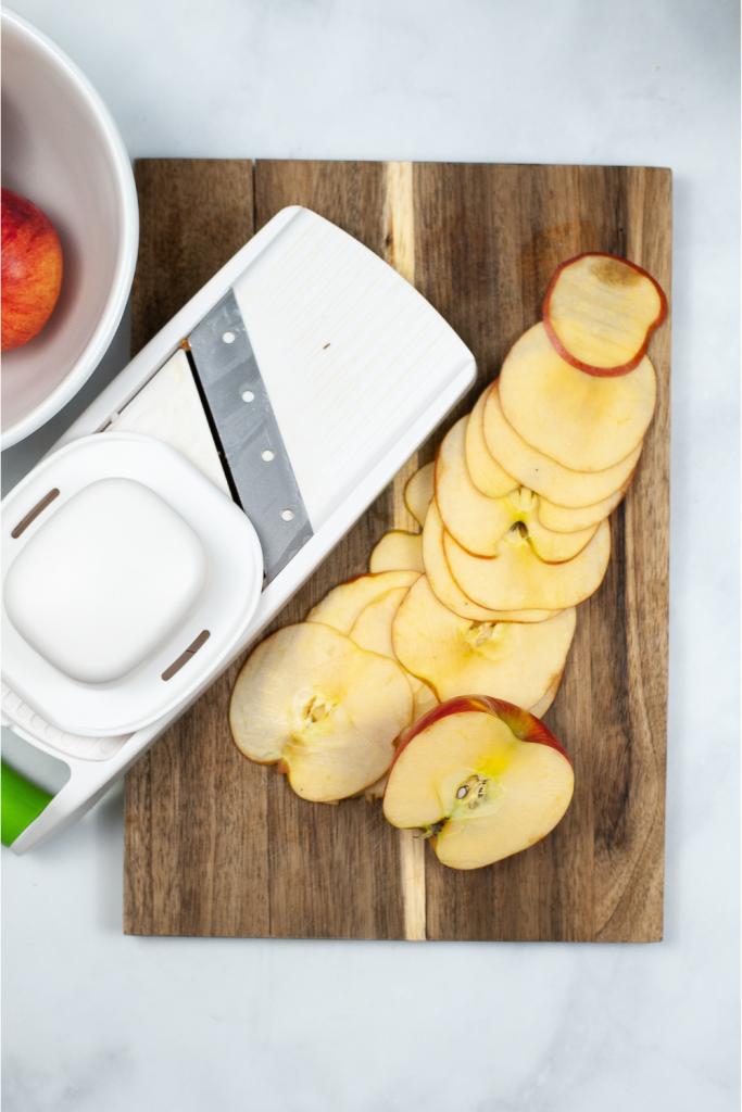 Slicing the apples with a mandoline slicer.