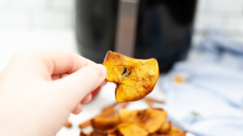A hand holding up a single cinnamon and sugar apple chip from the air fryer