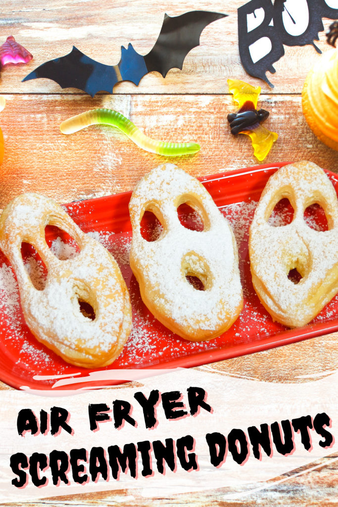 Title image of screaming donuts on a red plate on a wooden table flat lay with Halloween trinkets and candy.
